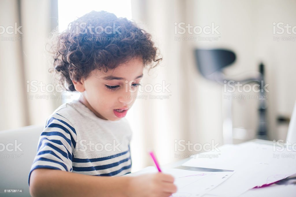 Middle eastern boy doing his homework and drawing. stock photo