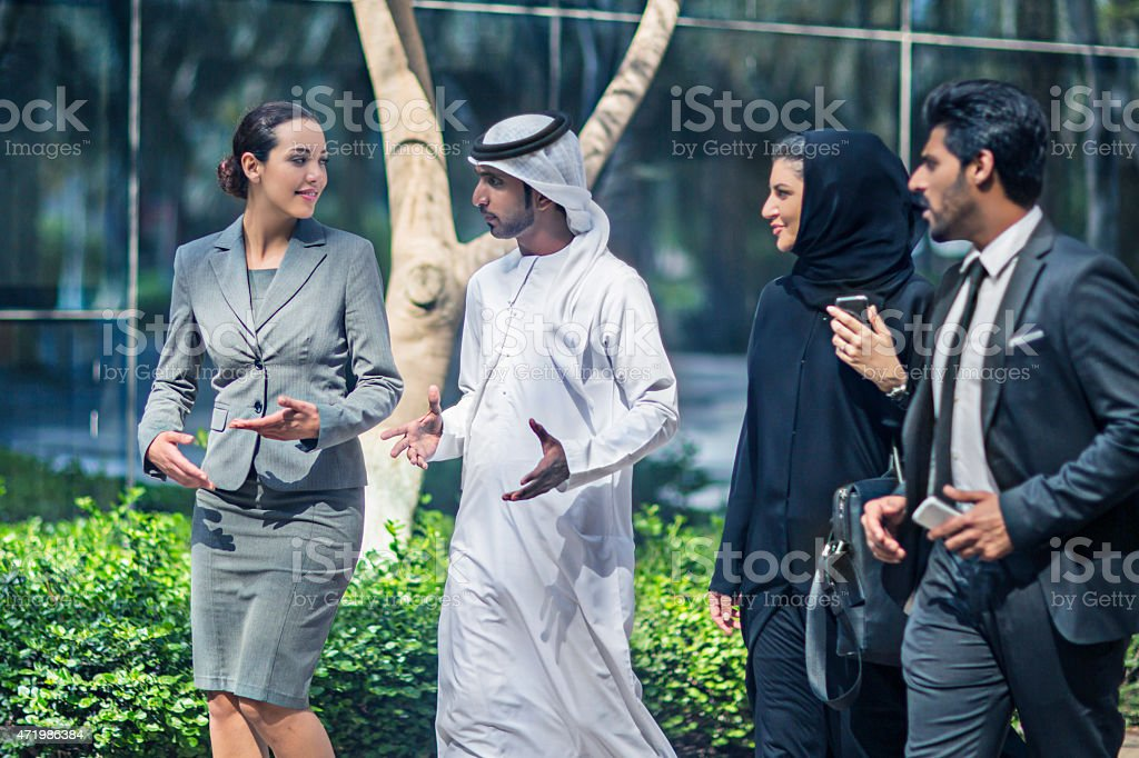 Middle Eastern business people talking in the street stock photo
