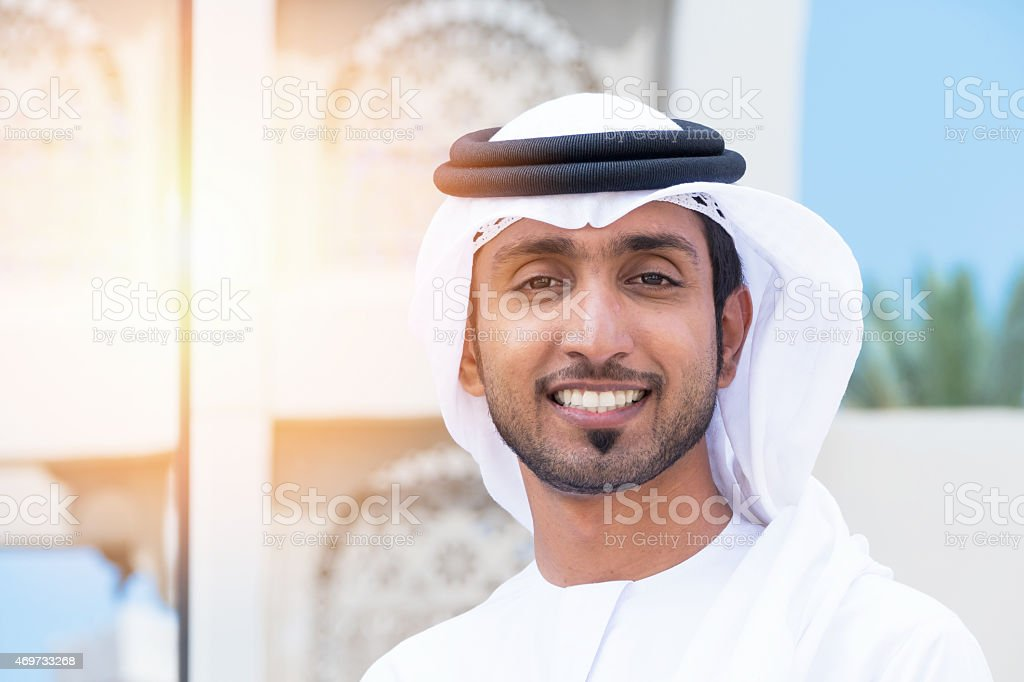 Middle Eastern businessman standing outside an office block and smile stock photo