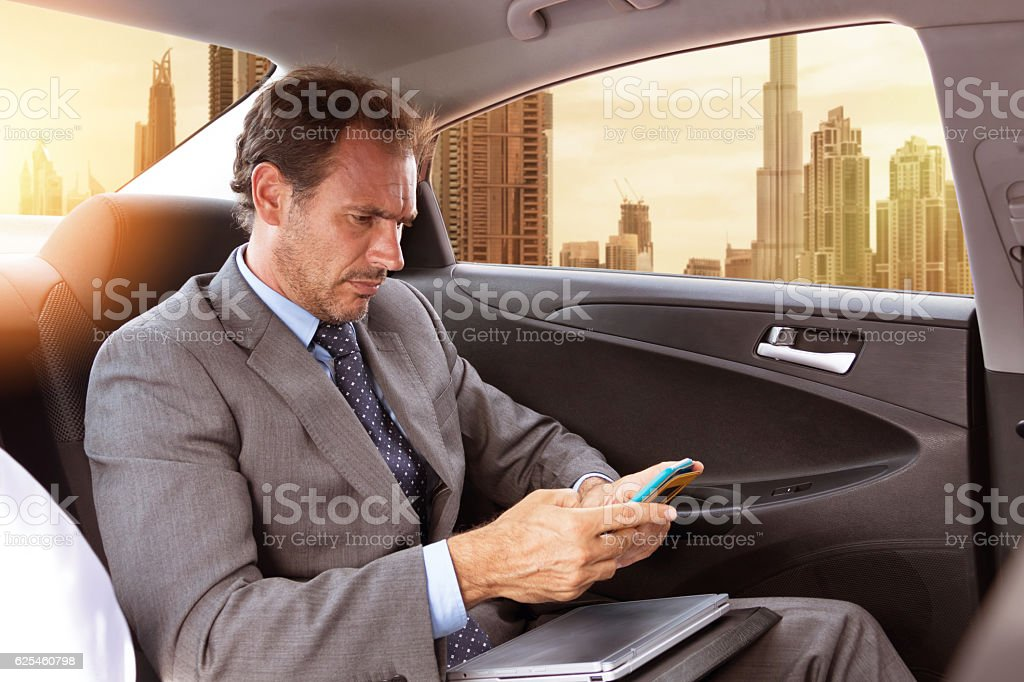 Middle eastern businessman traveling in car stock photo