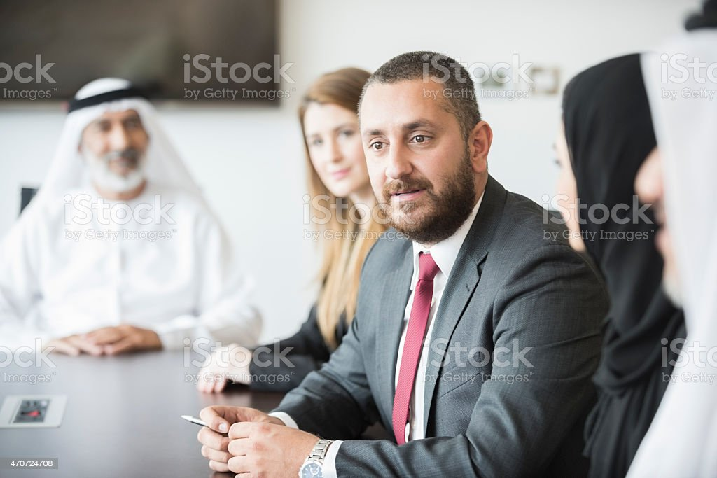 Middle Eastern businessman with colleagues at conference table stock photo