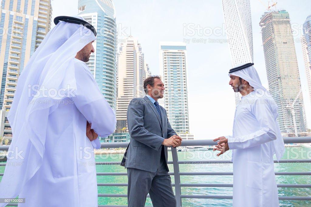 Middle eastern businessmen meeting western man in Dubai stock photo