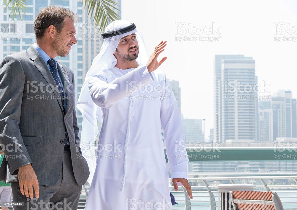 Middle eastern businessmen meeting western man stock photo