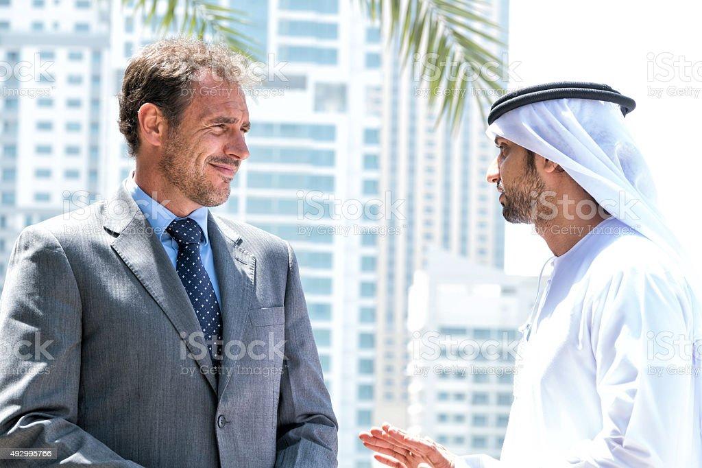 Middle eastern businessmen meeting western man stock photo