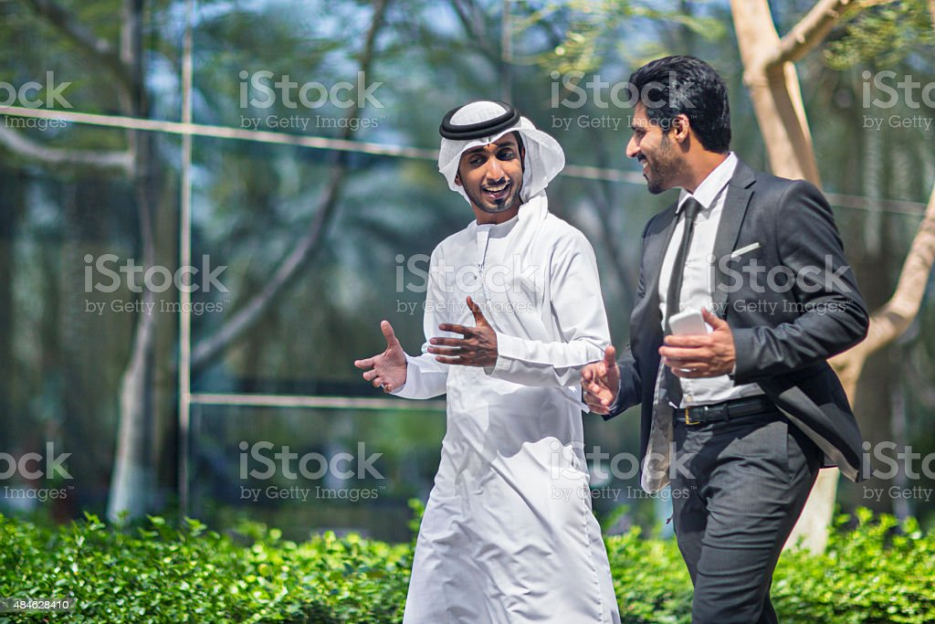 Middle Eastern businessmen talking in the street stock photo