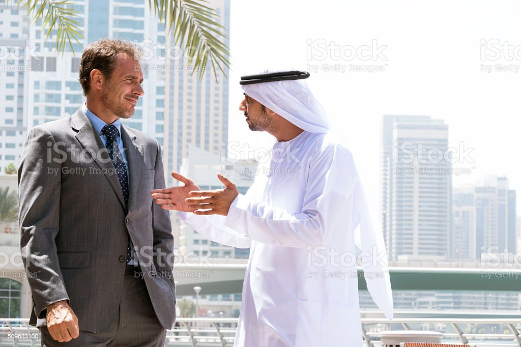 Middle eastern businessmen talking with western man stock photo