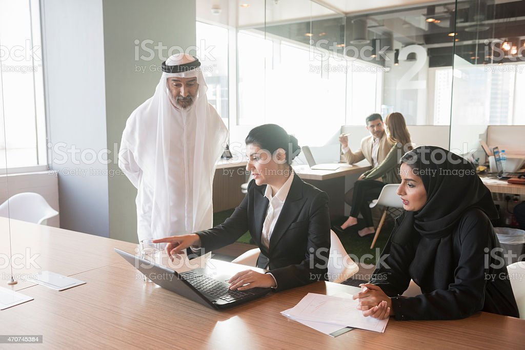 Middle Eastern businesswoman discussing over laptop with team stock photo