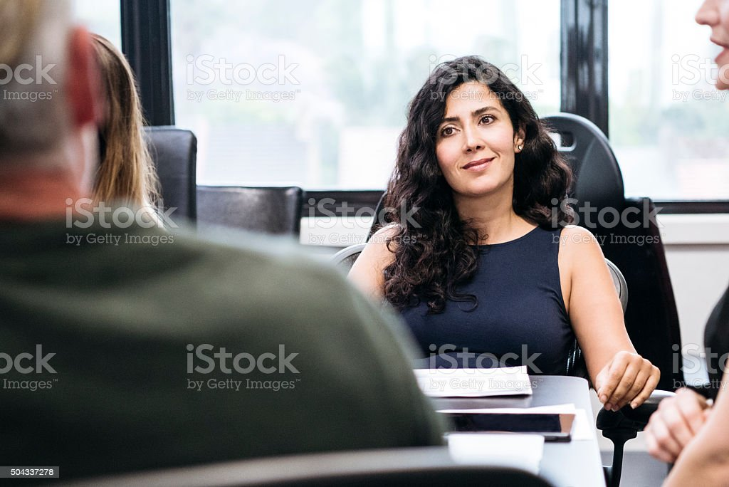 Middle Eastern businesswoman in meeting with male colleague stock photo