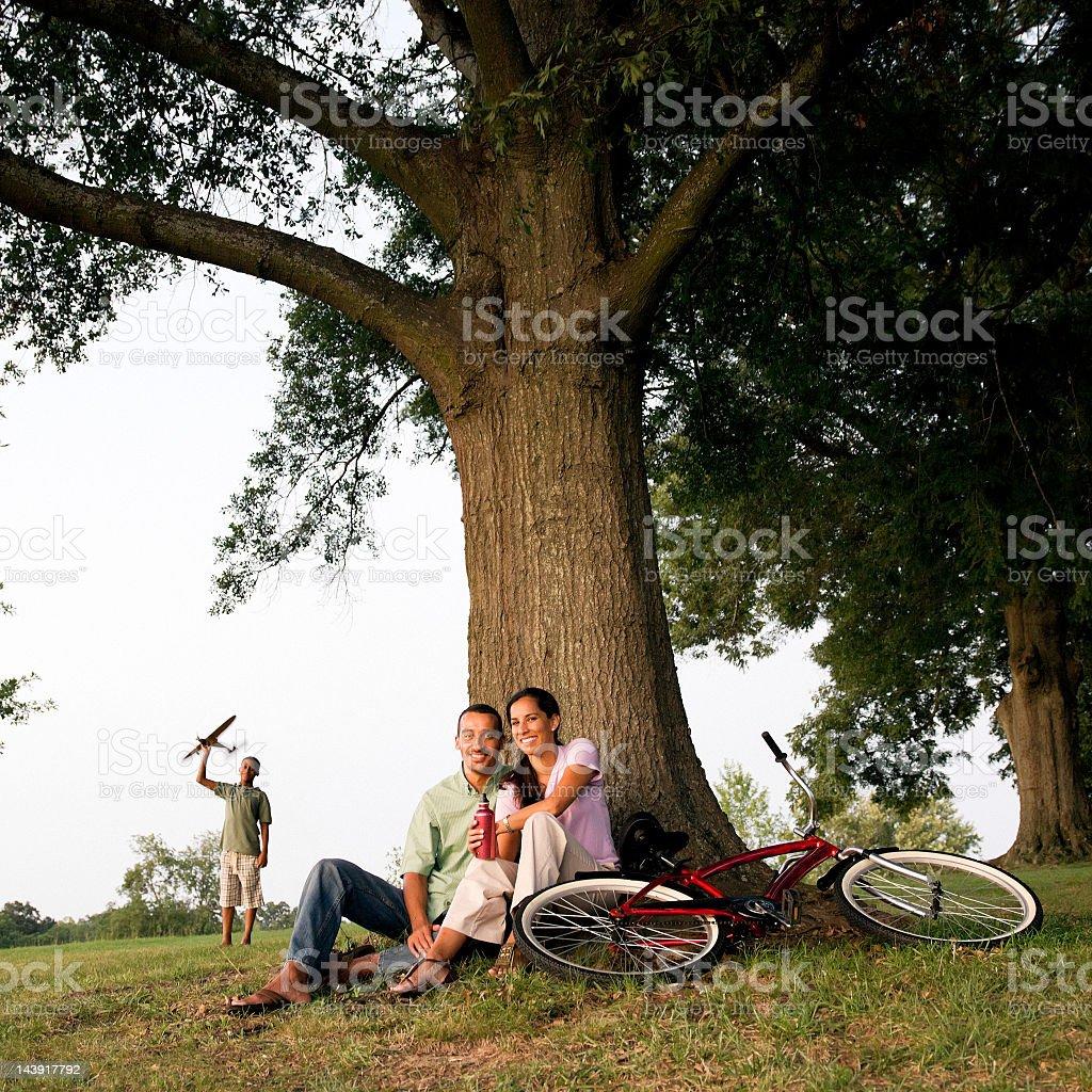 Middle Eastern couple Sitting Under Large Tree stock photo