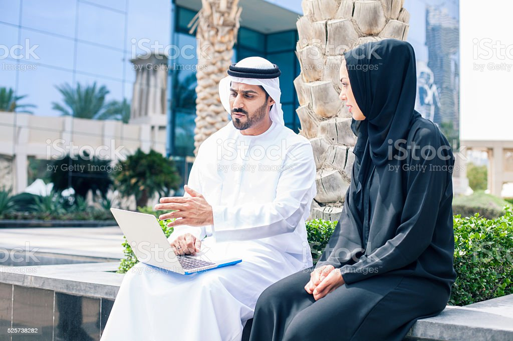 Middle eastern couple using laptop outside an office building stock photo