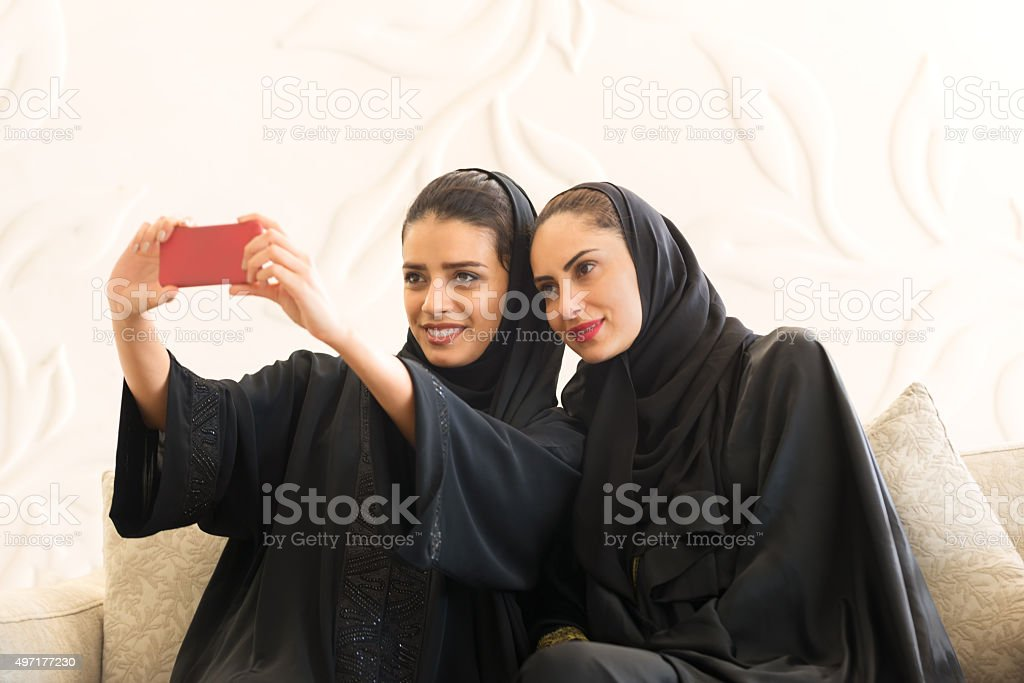 Middle Eastern Emirrati Women Taking Selfie in Modern White Room stock photo
