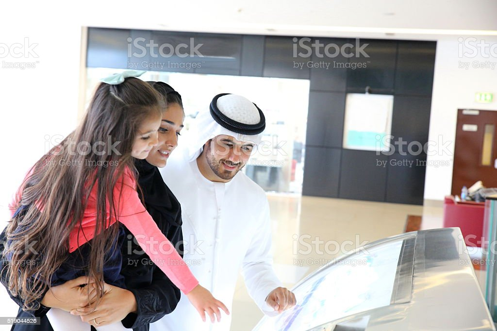 Middle Eastern family in shopping mall stock photo