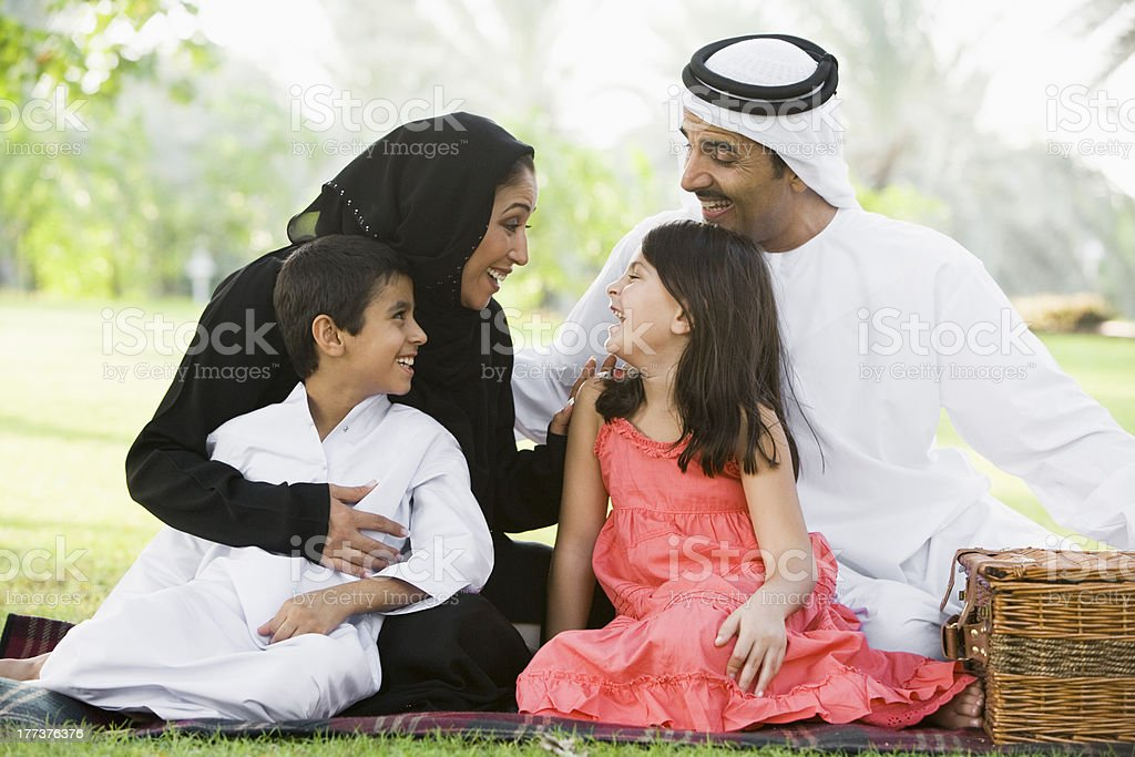 Middle Eastern family sitting in a park stock photo