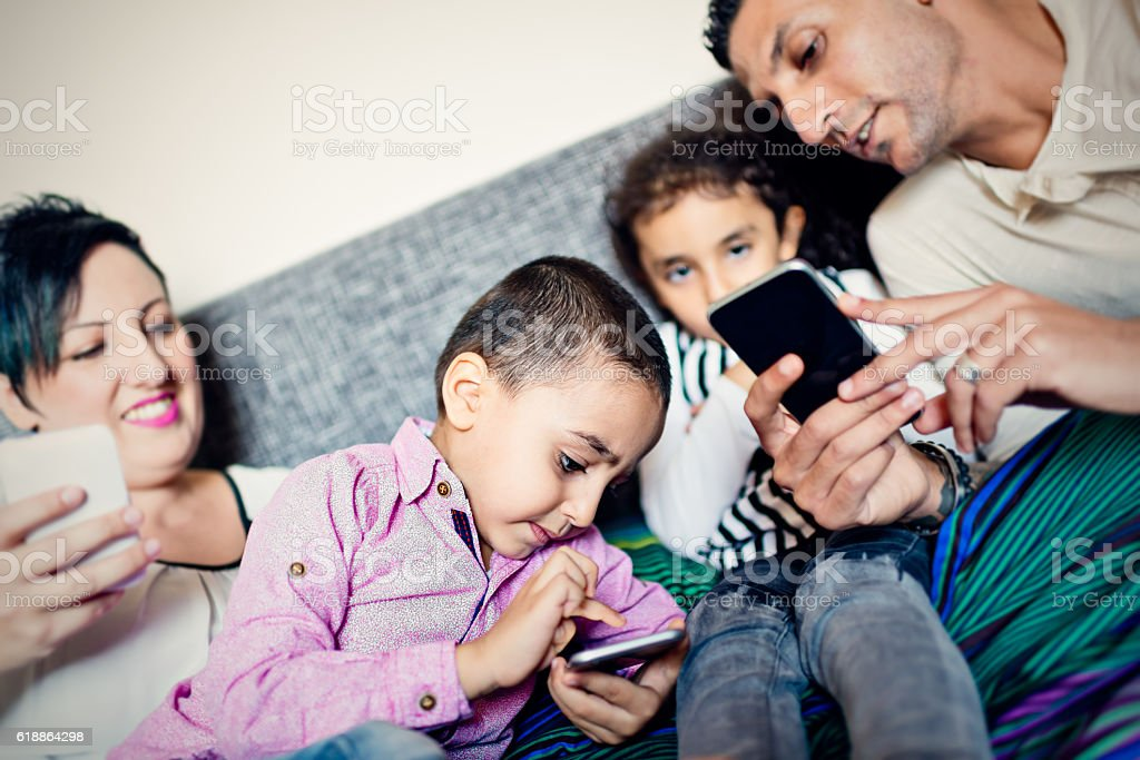 Middle Eastern family using smartphones stock photo