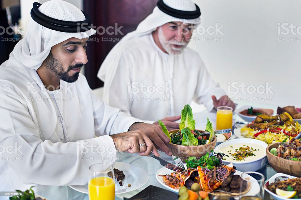 Middle Eastern father and son eating lunch stock photo