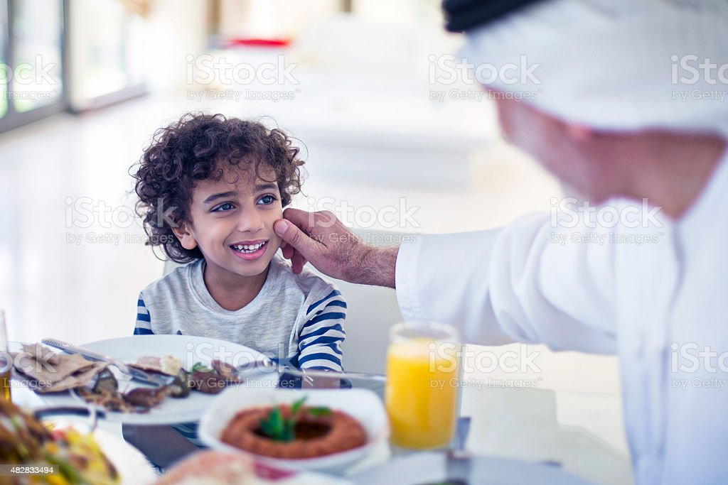 Middle Eastern grandfather talking with his grandson while eating stock photo