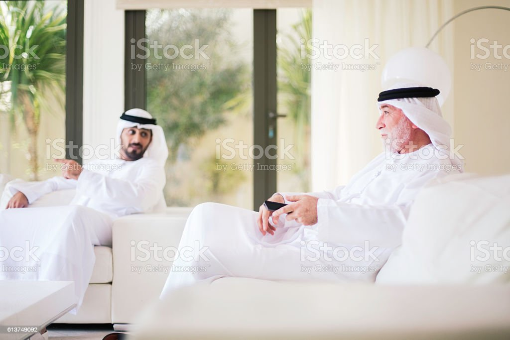 Middle eastern grandfather watching tv at home with grandson. stock photo