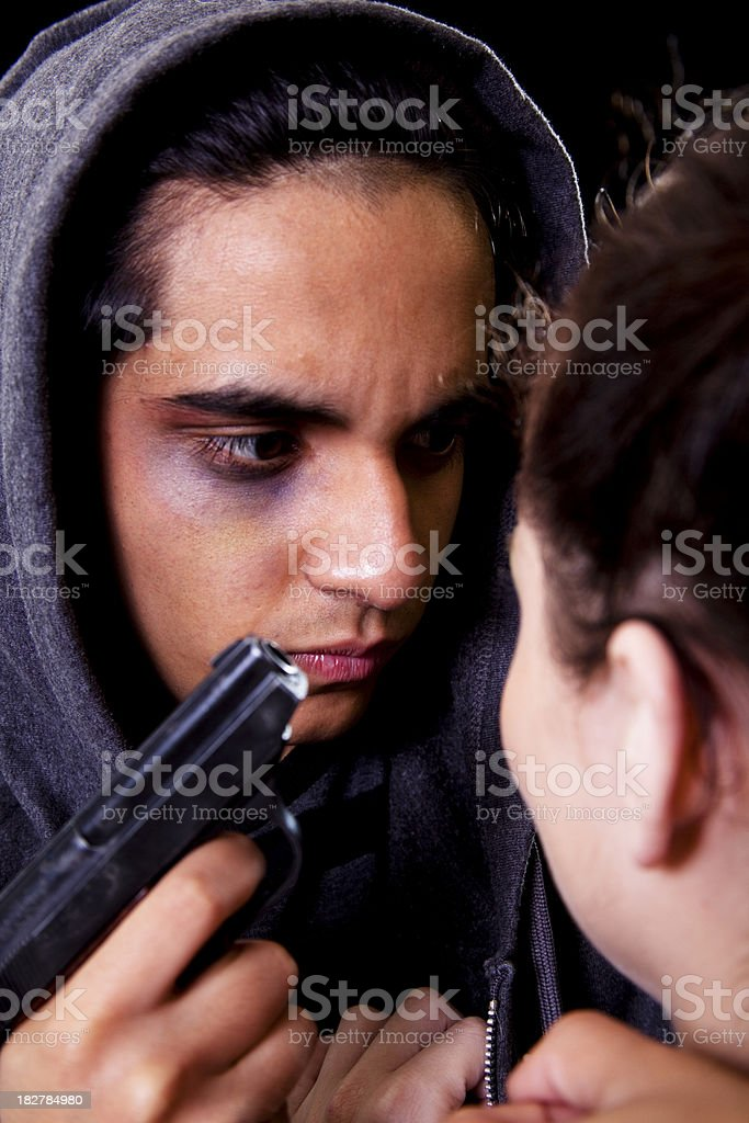 Middle Eastern male threatening caucasian female with gun royalty-free stock photo