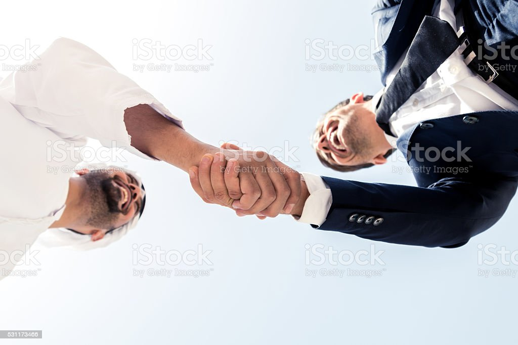 Middle Eastern Man and European Business Man Shaking Hands stock photo