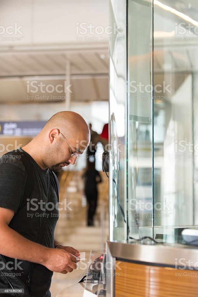 Middle Eastern Man Buying Train Ticket at Station, Dubai, UAE stock photo