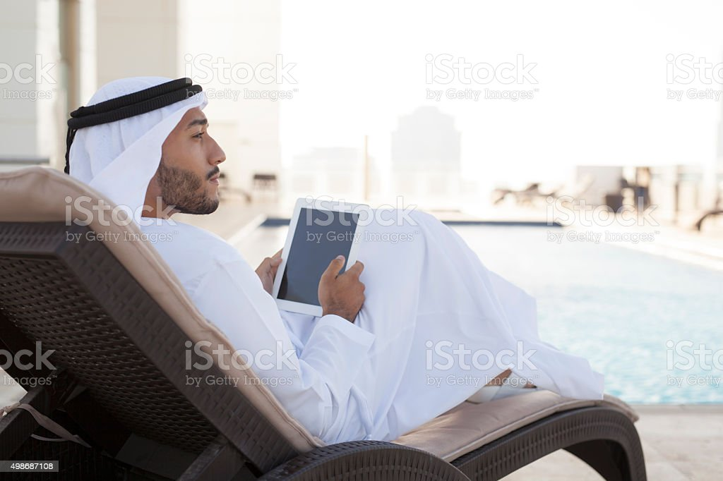 Middle Eastern Man Contemplating by the Pool with iPad stock photo