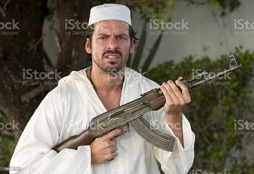 Middle Eastern Man Dressed in White and Armed with Gun stock photo