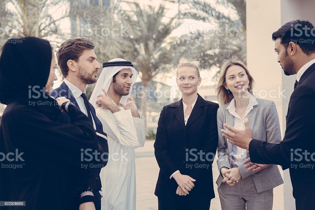 Middle Eastern Man in Suit Leading The Conversation Outdoors stock photo