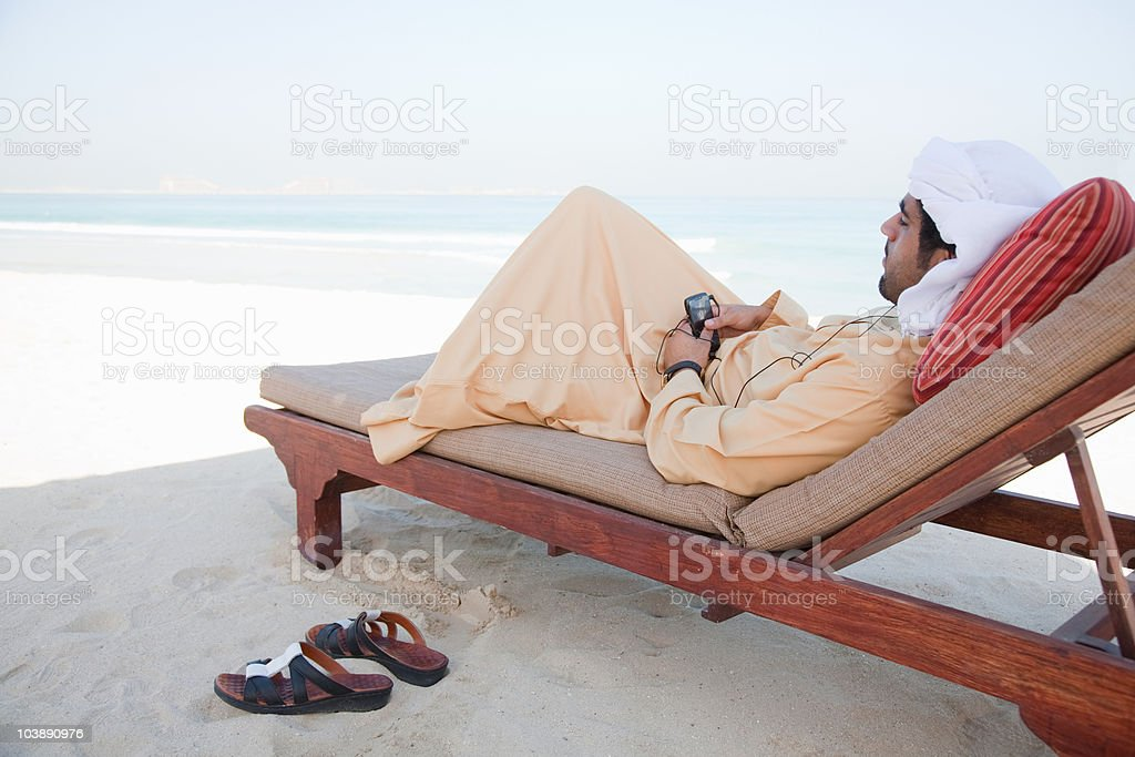Middle Eastern man listening to music on mobile phone royalty-free stock photo