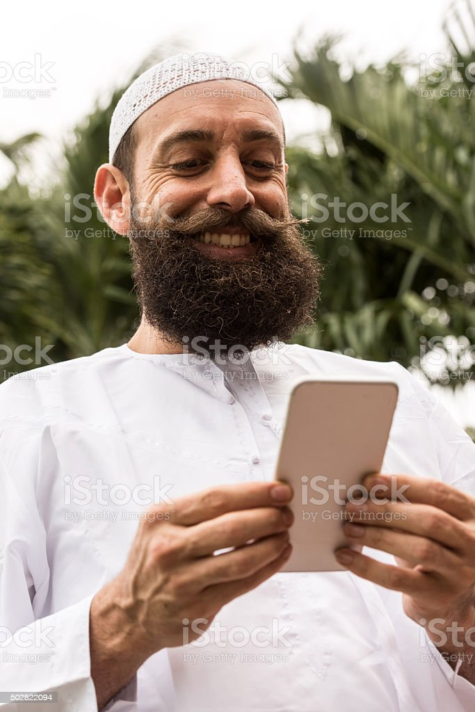 Middle eastern man looking at his smart phone stock photo