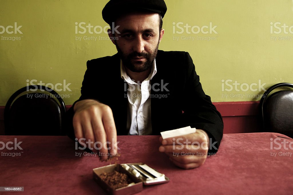 middle eastern man rolling cigarettes stock photo