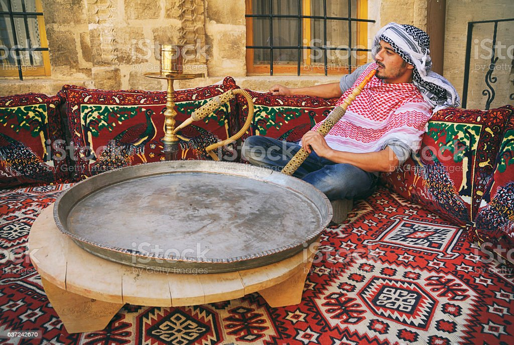 Middle Eastern Man Smoking Hookah on a Traditional Couch stock photo