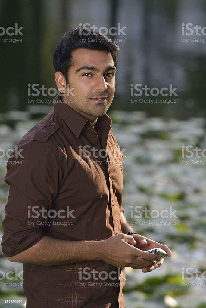 Middle Eastern man with his phone in the park royalty-free stock photo