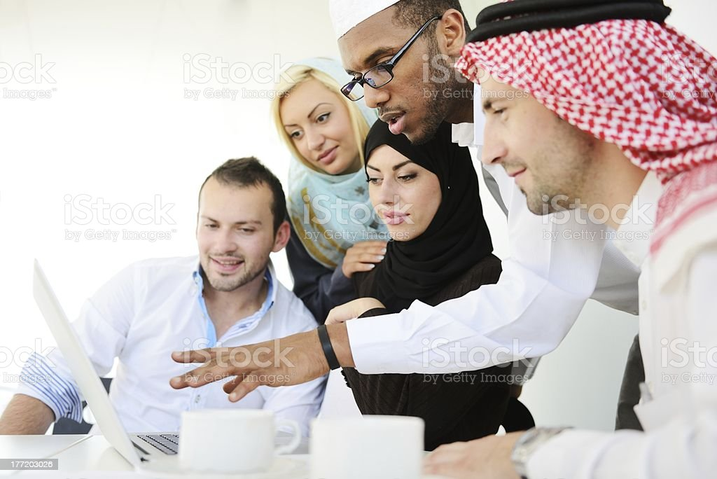 Middle eastern people in traditional garb around a laptop royalty-free stock photo