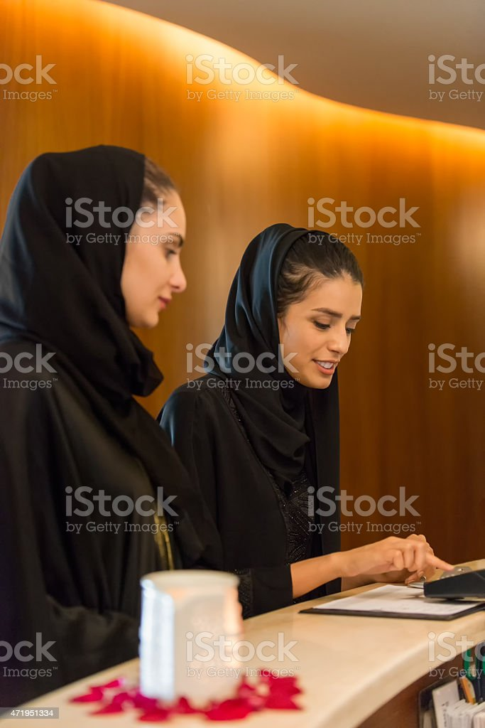 Middle Eastern Woman at Counter Paying by Credit Debit Reader stock photo