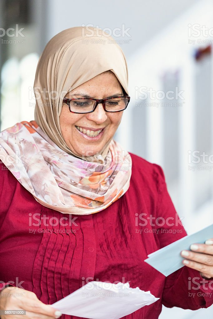 Middle eastern woman cheking the mail stock photo