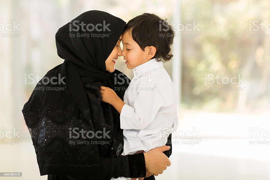 middle eastern woman playing with her son stock photo