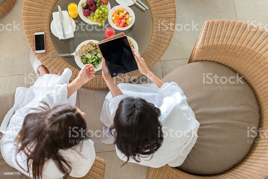 Middle Eastern Women Friends Reviewing Tablet Computer at Spa Lunch stock photo