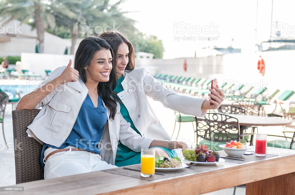 Middle Eastern Women Taking Selfie, Poolside Café, Luxury Hotel, Dubai. stock photo
