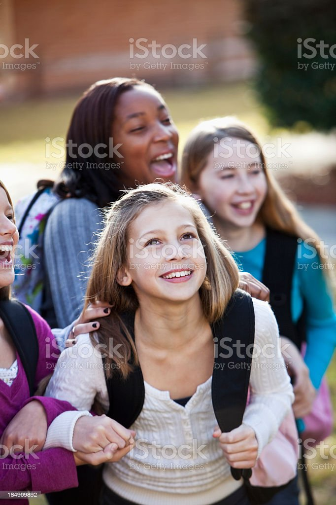 Middle school girls with bookbags outside stock photo