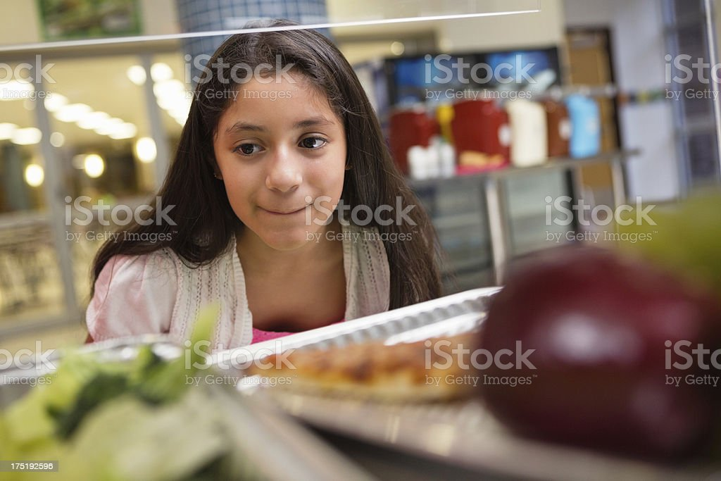 Middle school student choosing healthy /unhealthy food in lunch line royalty-free stock photo