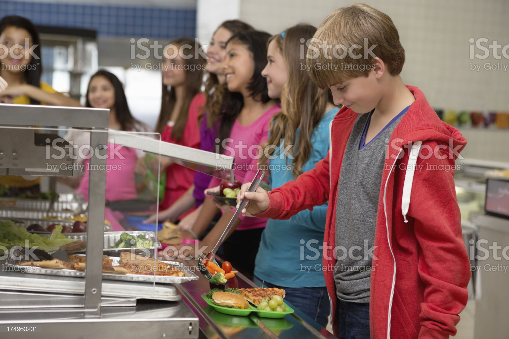 Middle school students choosing healthy food in cafeteria lunch line royalty-free stock photo