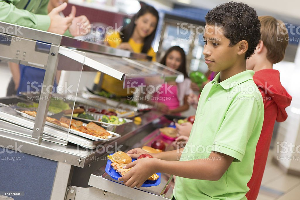 Middle school students getting lunch items in cafeteria line royalty-free stock photo