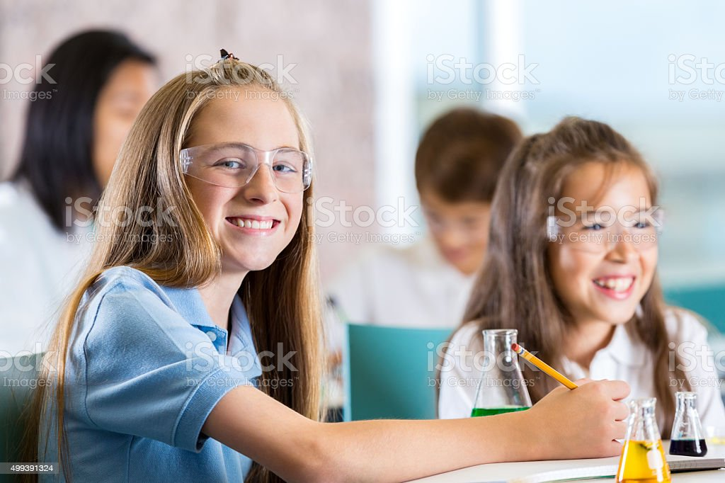 Middle school students using chemistry set in science class stock photo