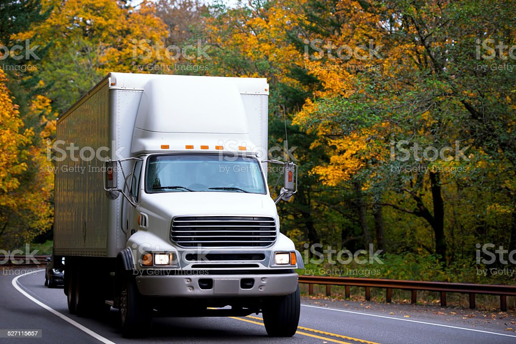 Middle size semi truck with box cargo on twisted highway stock photo
