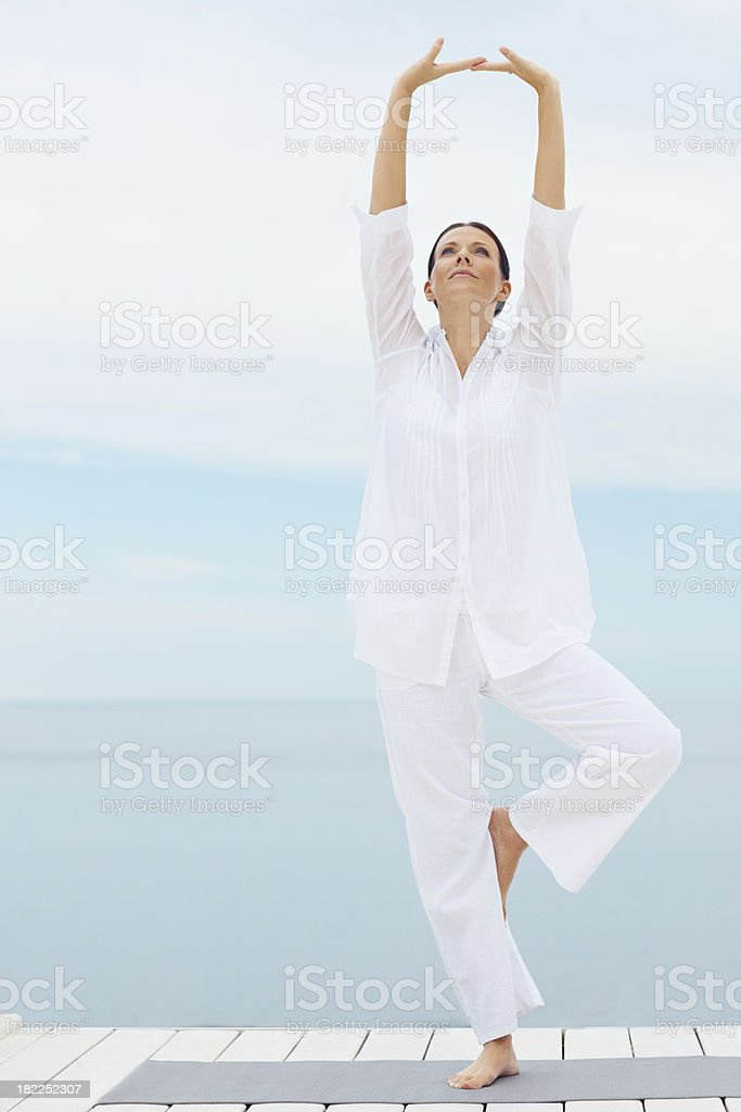 A middle-age lady practicing yoga outdoors wearing white royalty-free stock photo