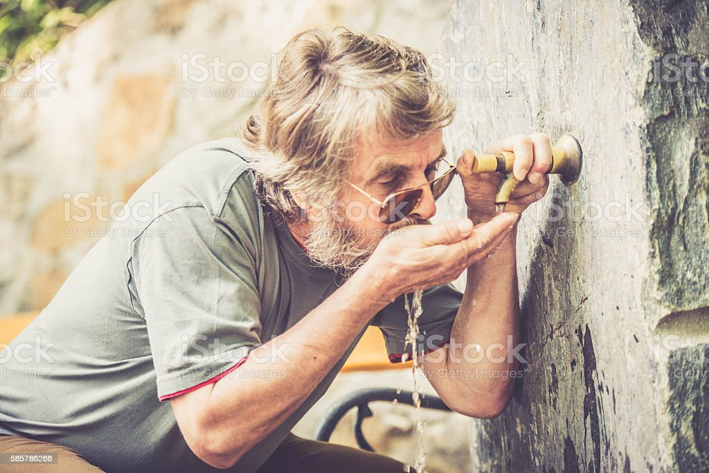 Middle-age man drinking water close up- refreshment break stock photo
