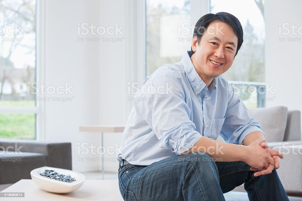 Middle-aged Asian man in living room stock photo