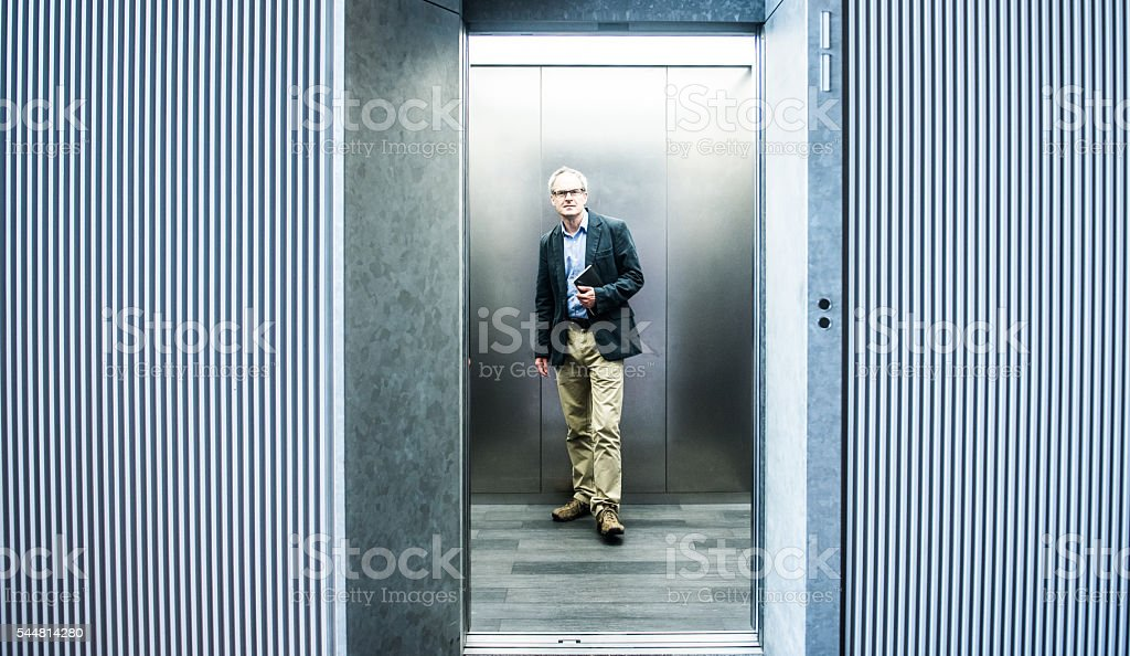 Middle-aged businessman in elevator stock photo