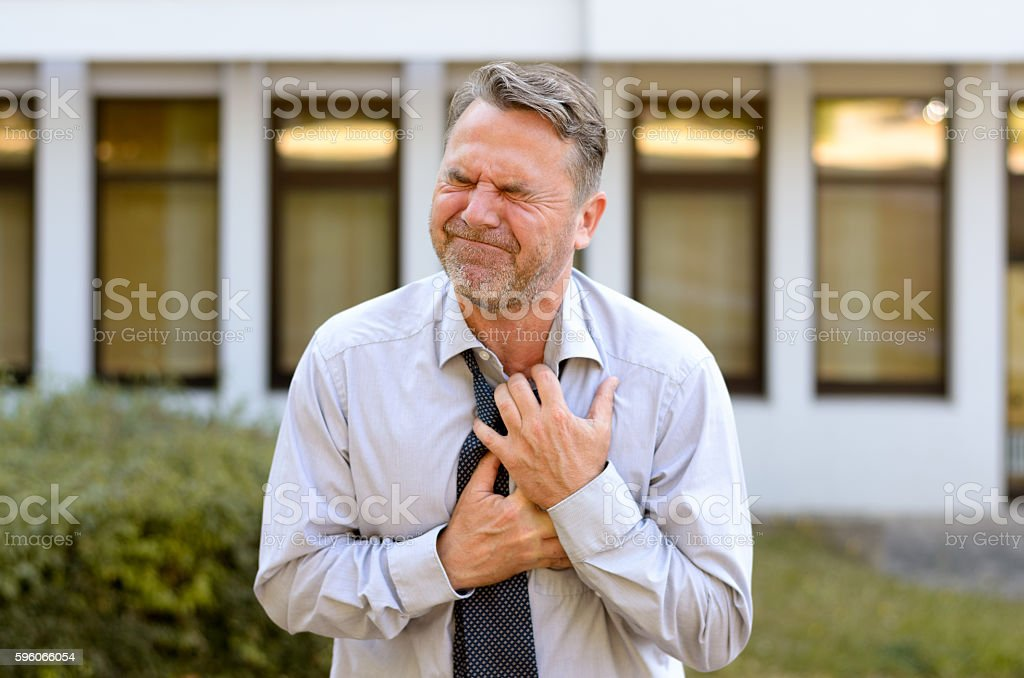 Middle-aged businessman suffering chest pains stock photo