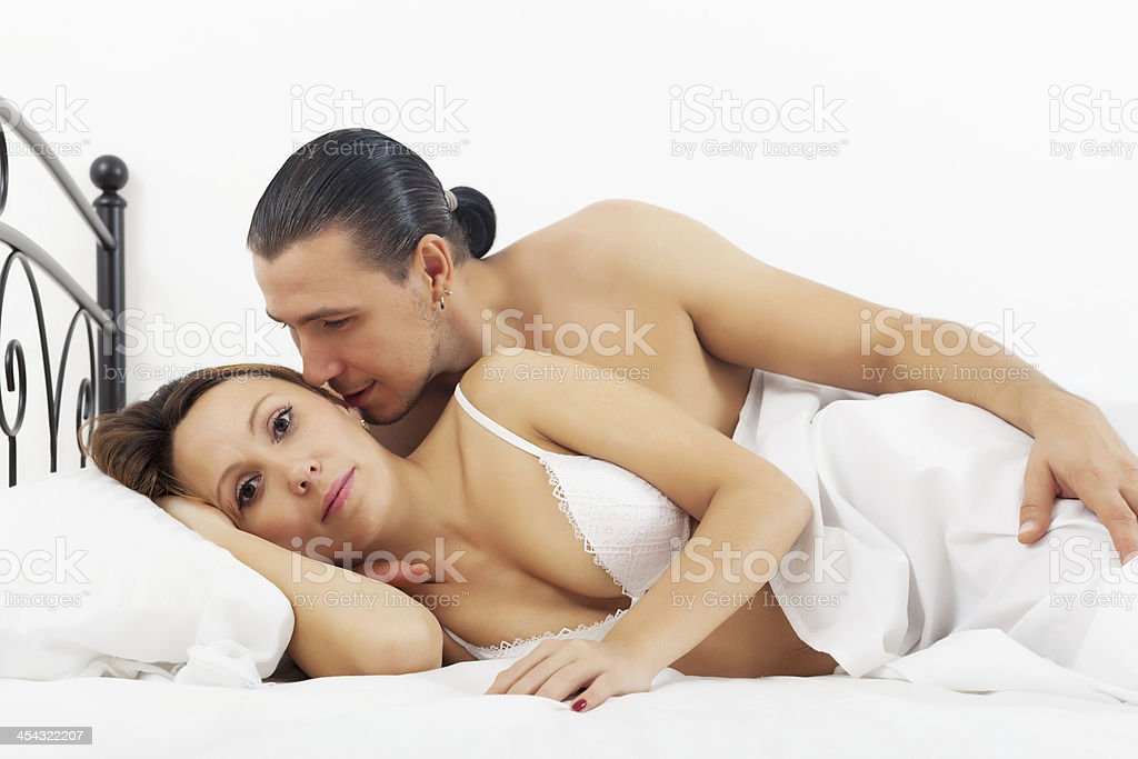 Middle-aged couple awaking in bed stock photo